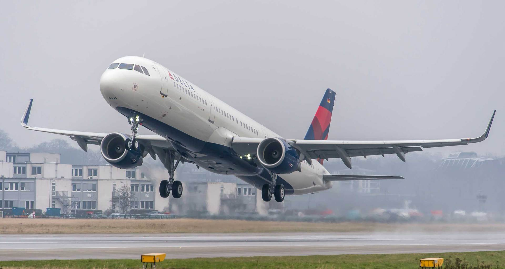 Delta Air Lines Airbus A321 taking off from foggy runway.