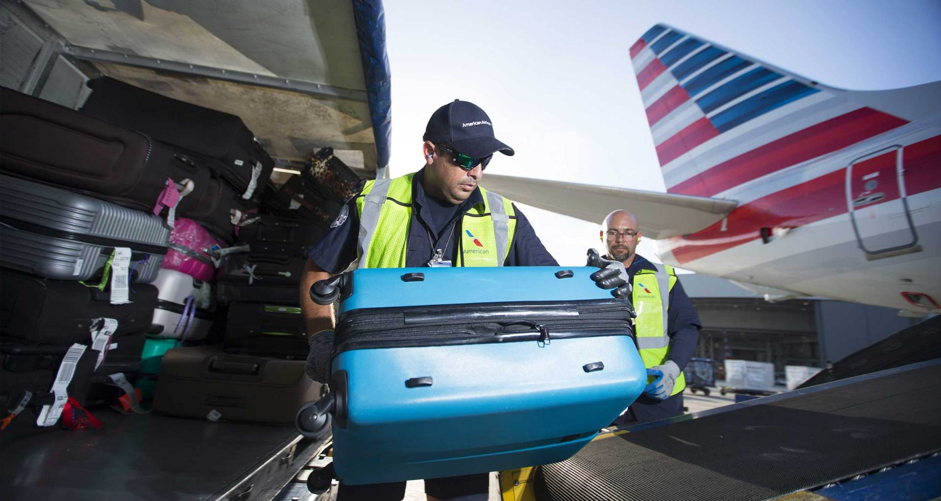 Baggage handler transferring suitcase from baggage cart into American Airlines airplane.