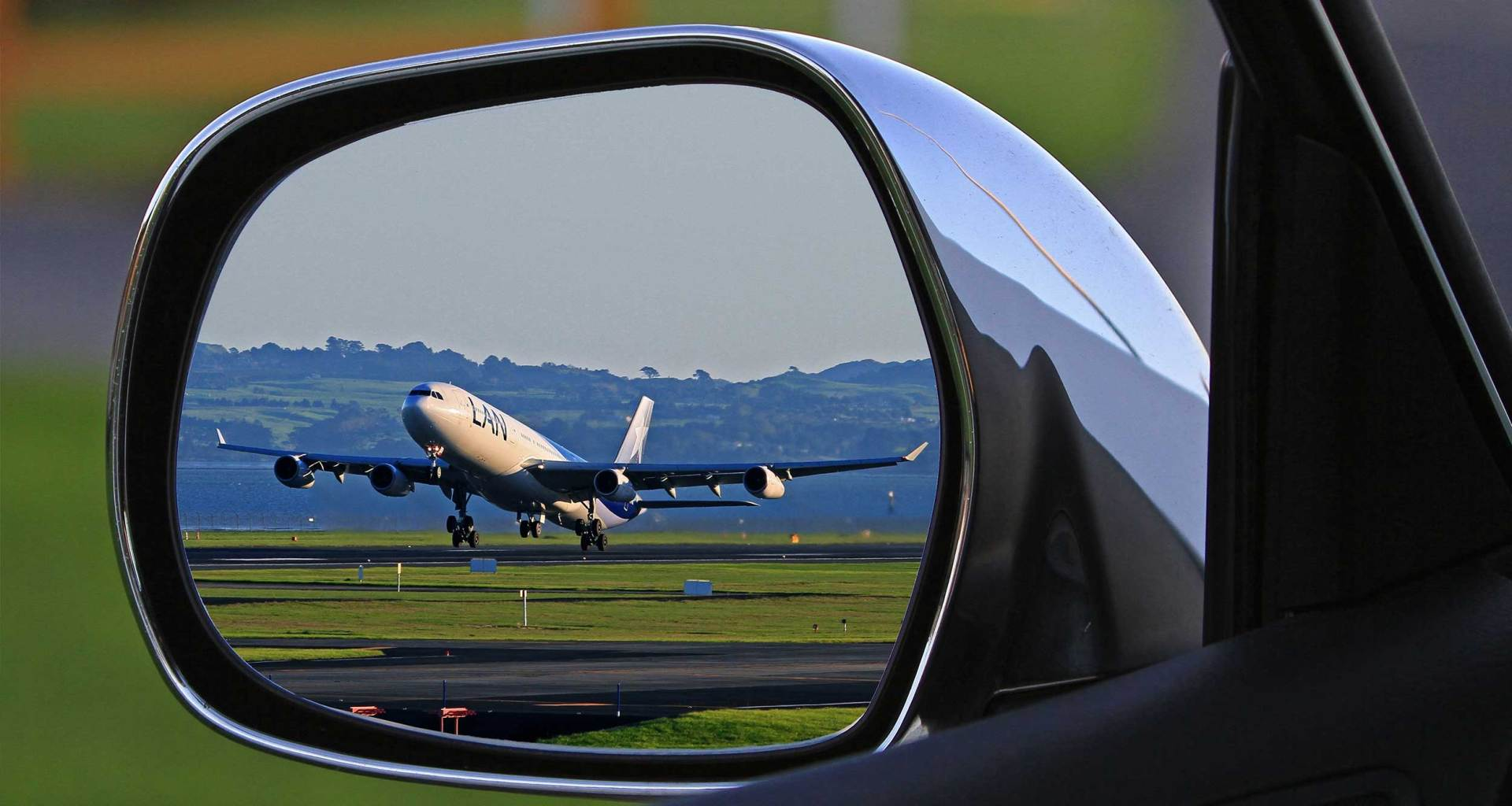 Airplane landing, reflection seen in a car's driver side mirror.