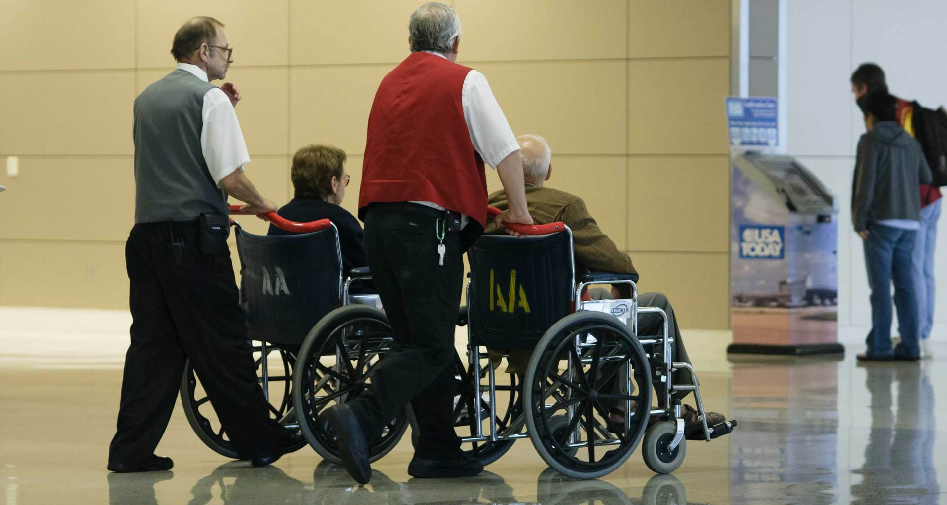 Two airline staff members pushing wheelchairs through the airport terminal.