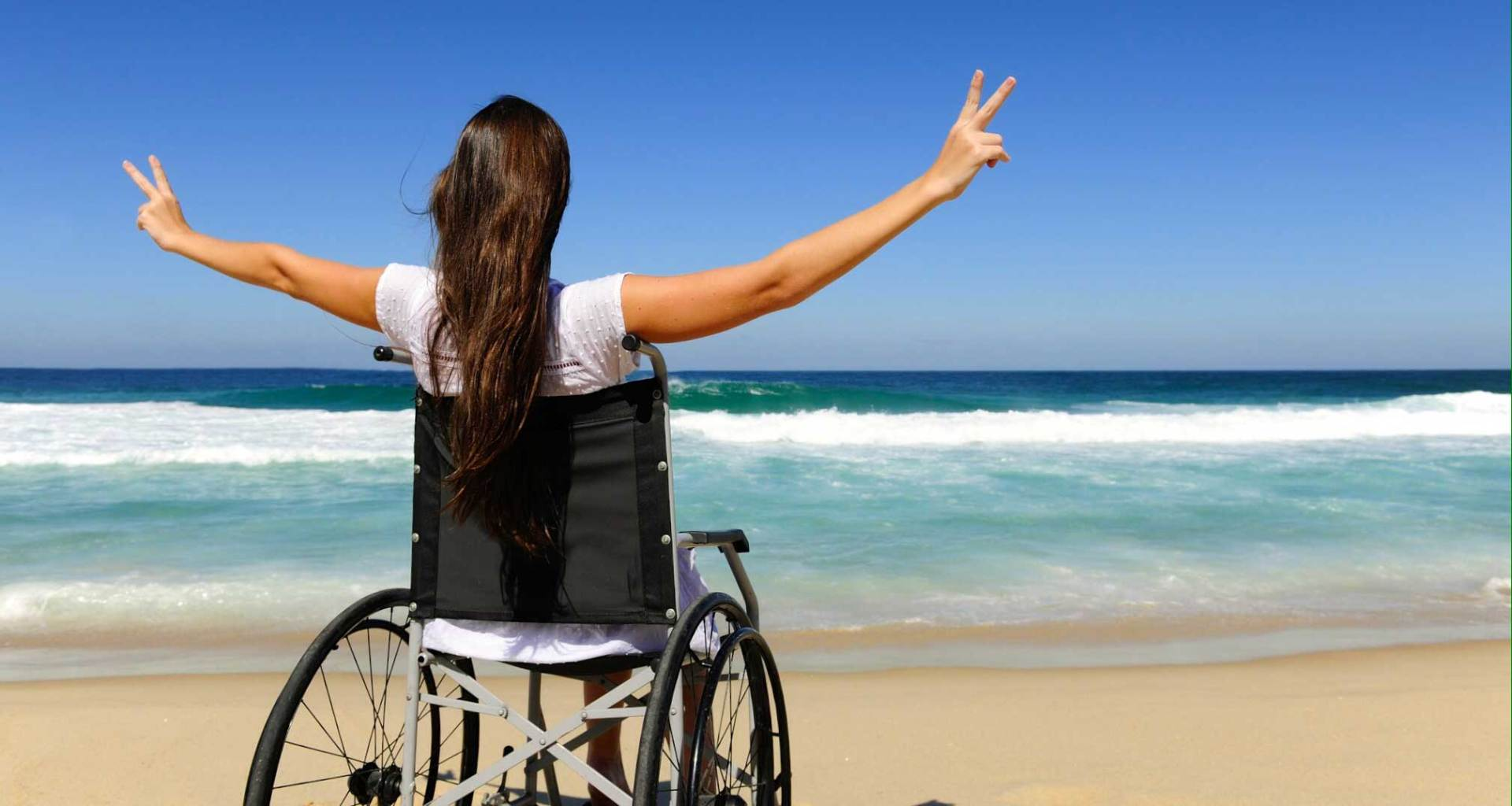 Stock photo of woman in wheelchair one beach with arms raised to heaven and hands making peace signs.