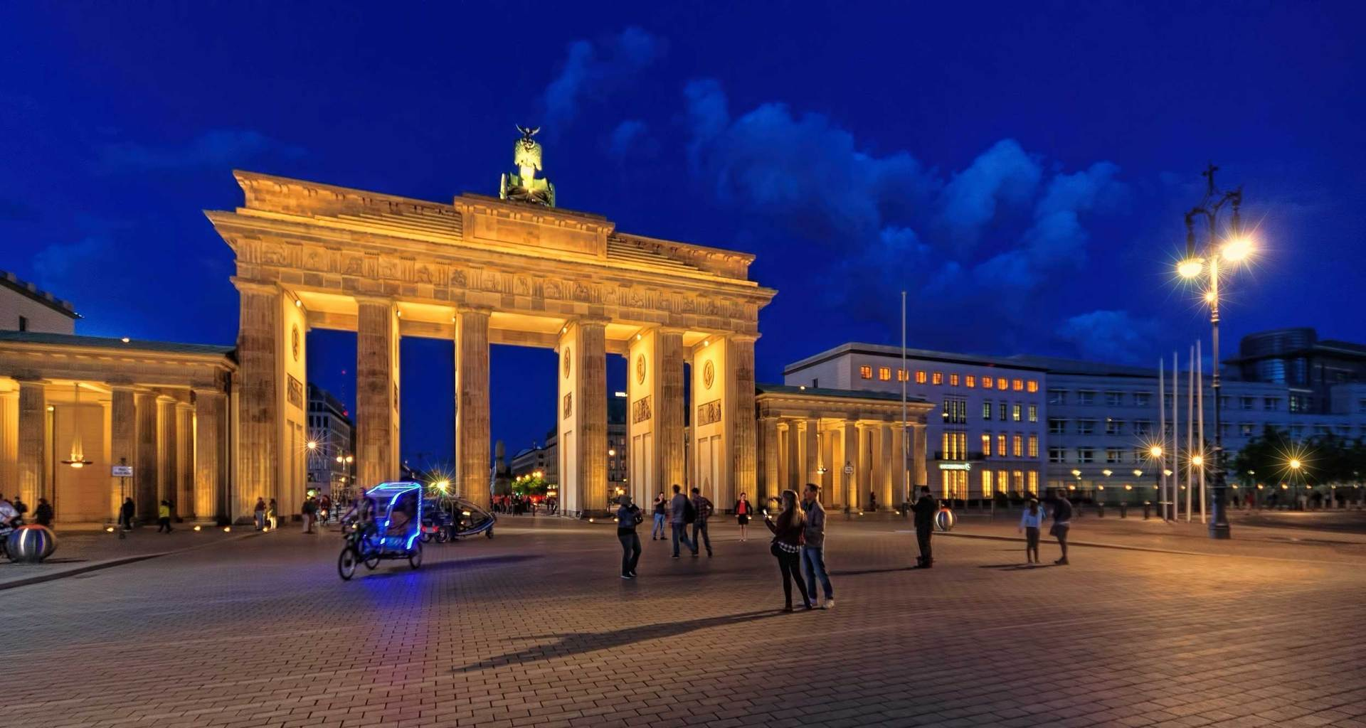 Brandenburg Gate against a dark blue sky at night.