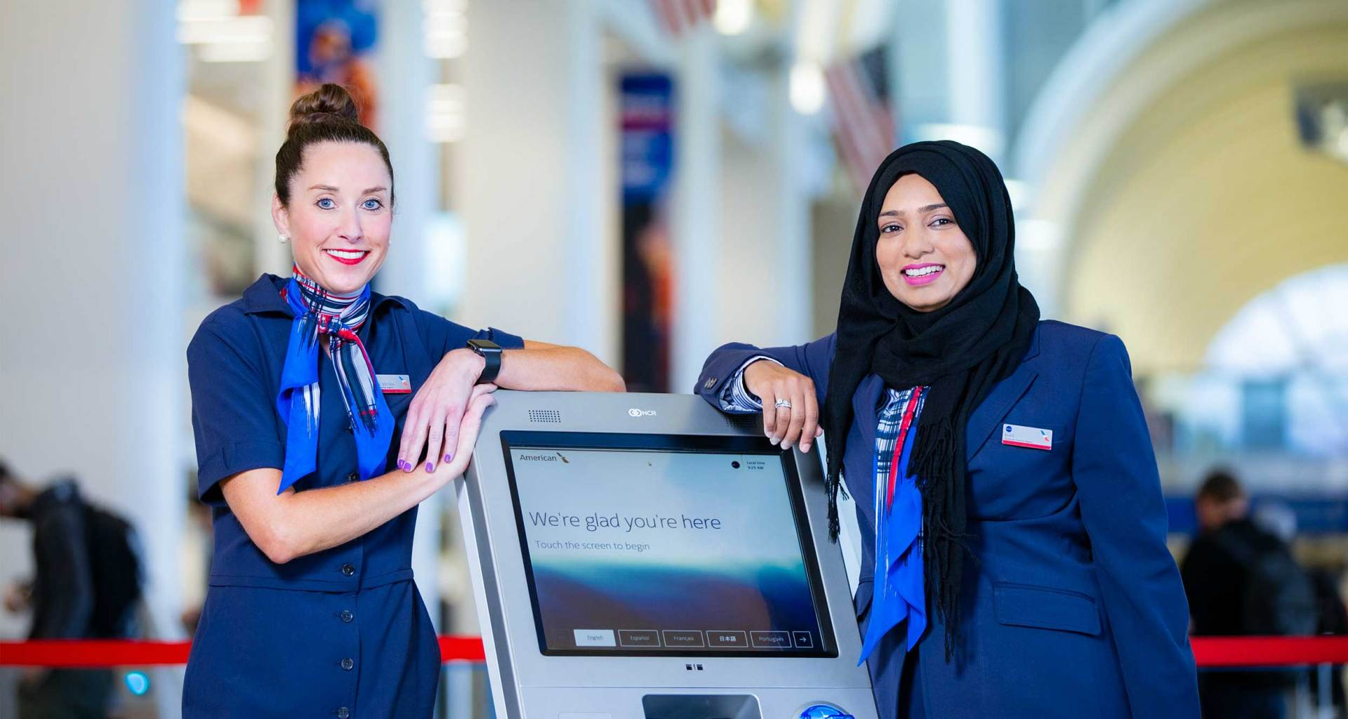 Two American Airlines team members standing at an airport kiosk.