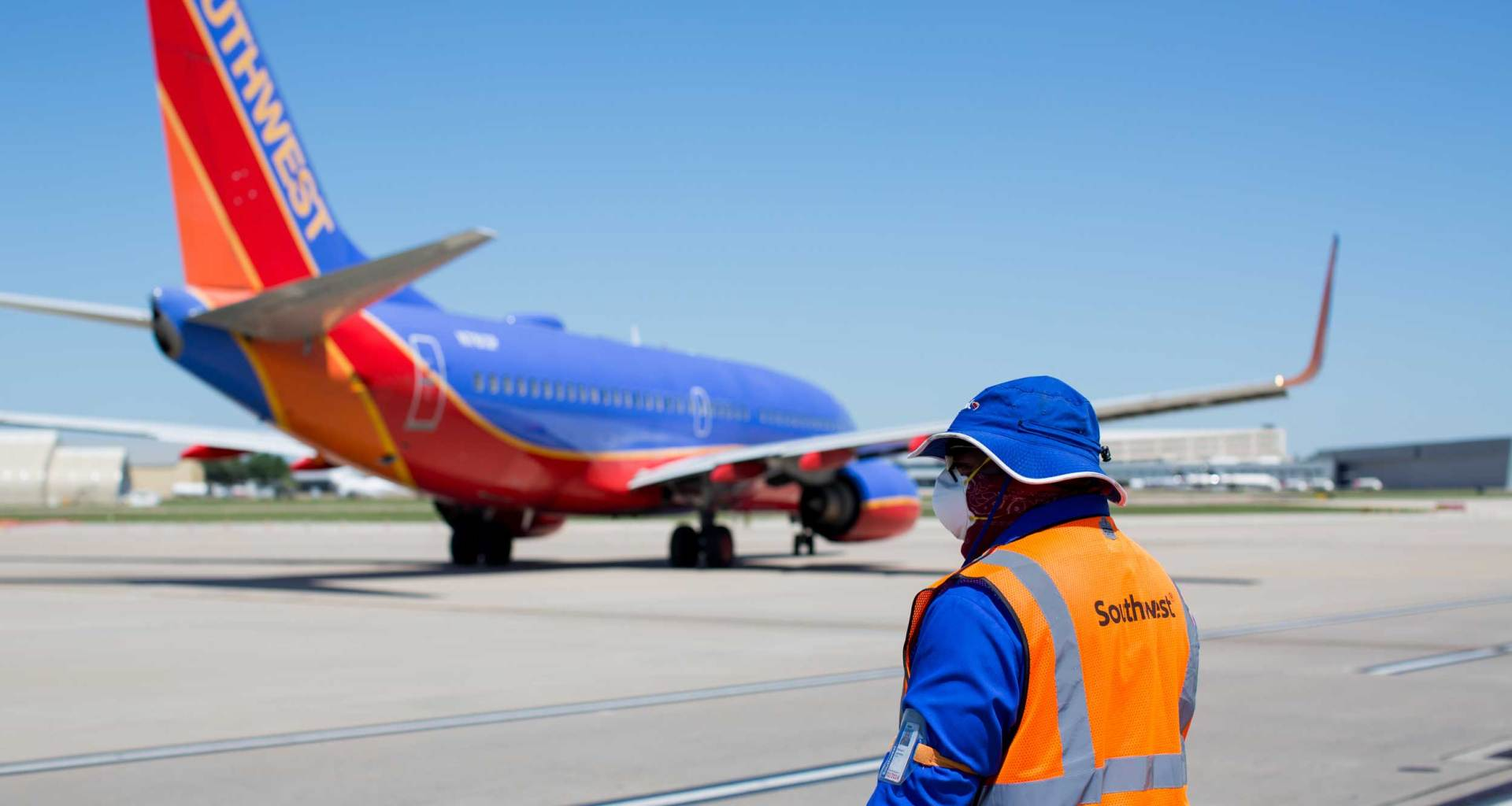 Airline employee watches from tarmac as Southwest Airlines jet taxis away.