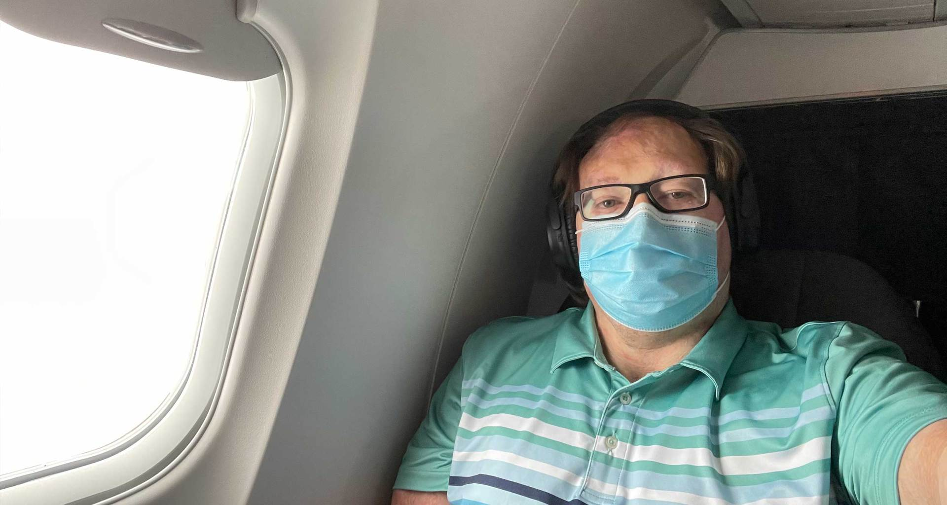 John takes selfie during flight while wearing face mask.
