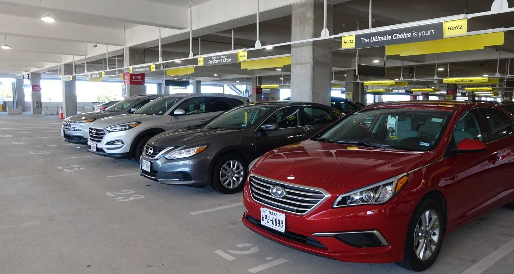 Rental cars lined up in a parking garage.