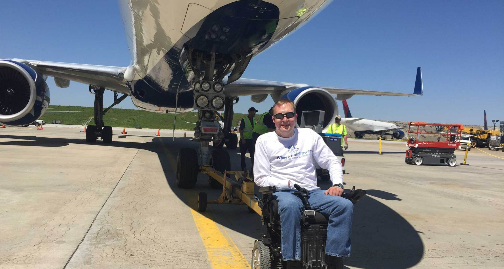 John seated in his wheelchair on the tarmac in front of a Boeing 757 airplane.