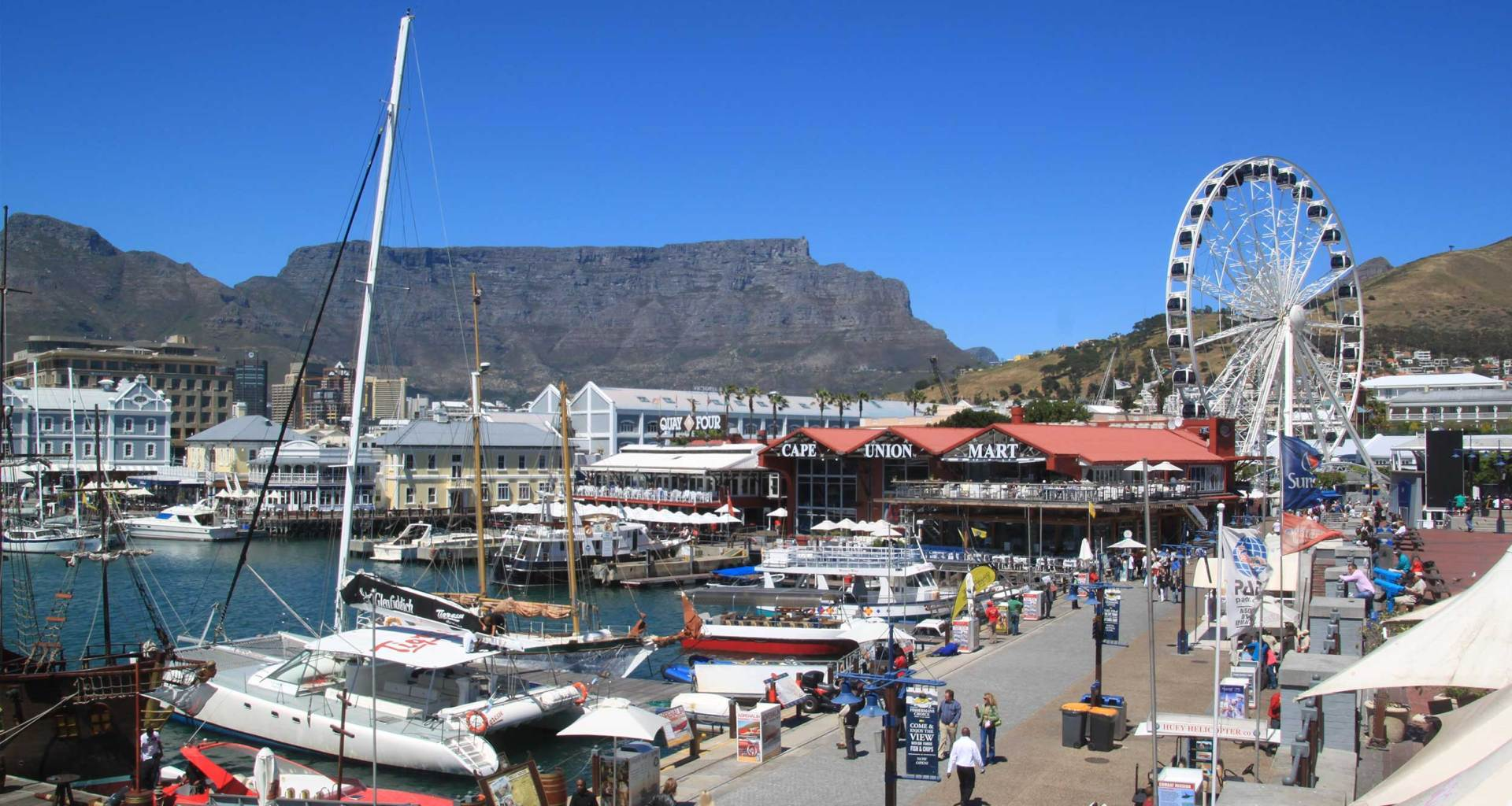 Cape Town boardwalk with Ferris wheel and mountain in background.