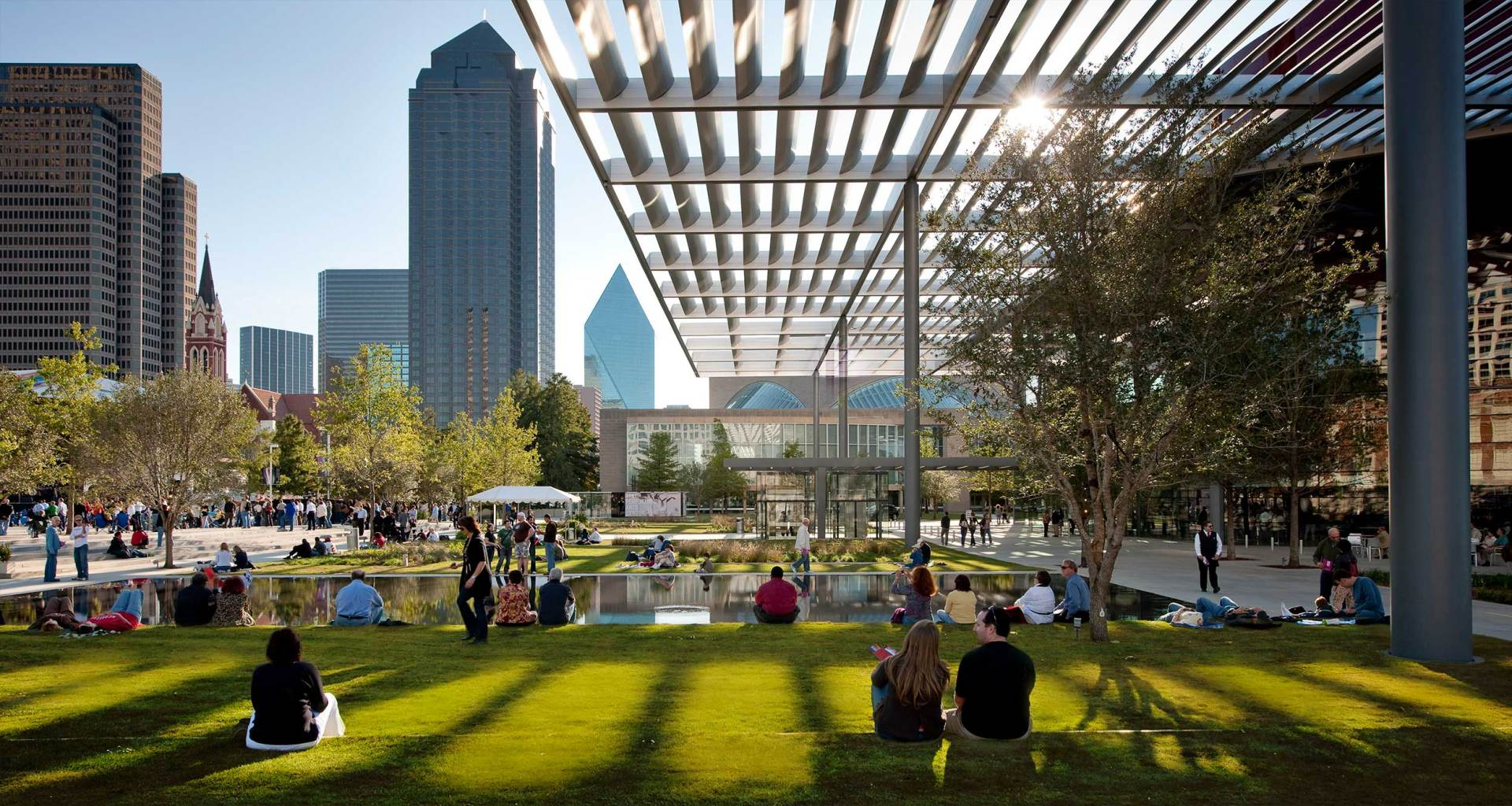 Public park in downtown Dallas, Texas, with trees, grass and shaded areas.