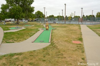 Mini-golf area with tennis and pickeball courts in the background.