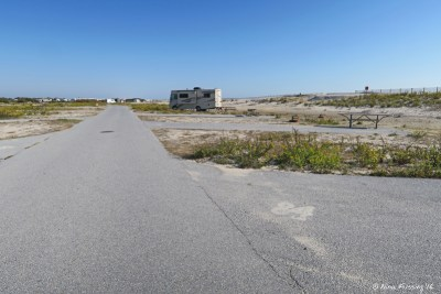 View down I loop on beach side. Empty site I84 on right with RV in I90 three sites behind.