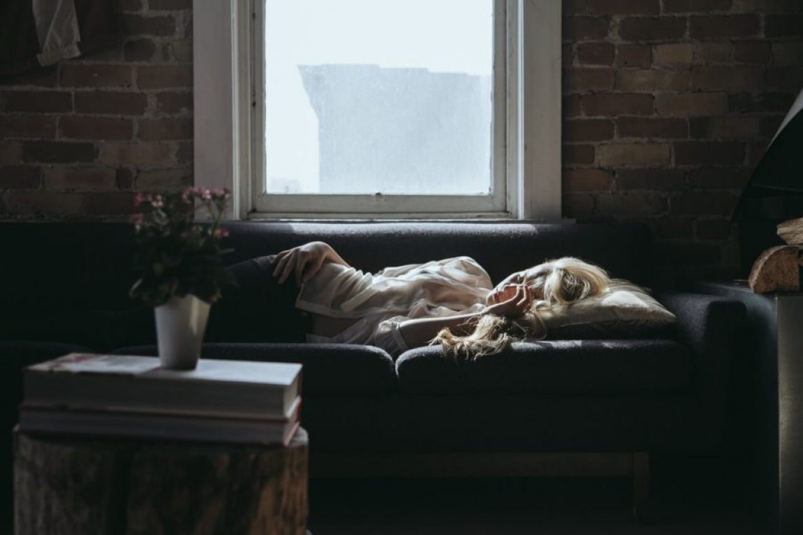 Woman with a headache on couch