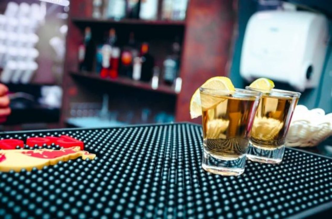 Two glasses full of alcohol, with lemon wedges, on a bar counter are not helping you overcome misconceptions about drug addiction