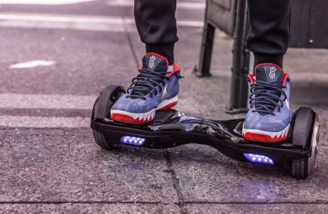 Black hoverboard with LED lights; user stands on it in running shoes