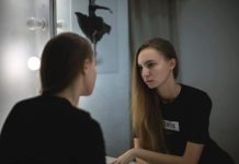 Young woman looks with a critical facial expression into mirror at her own reflection