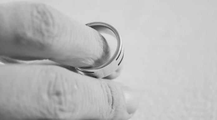 Closeup on wedding ring signals survive stress of divorce.