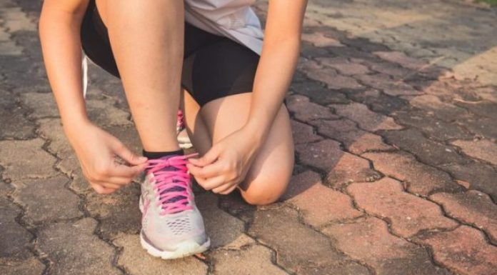 Getting fit for summer, this woman bends down to tie pink lace on her runner