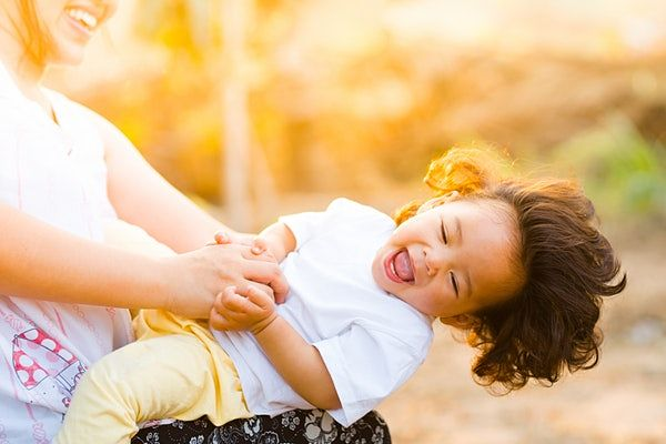 Cute kid laughing and happy as you have the best health insurance for your family.