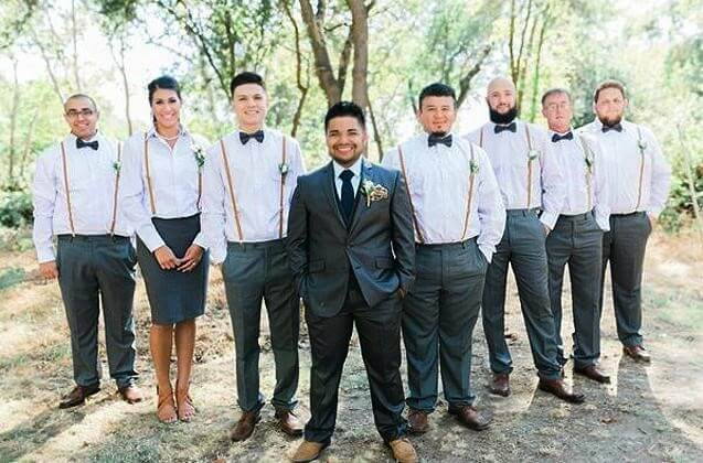 Woman matches the exact suit of the man's side of the wedding party.