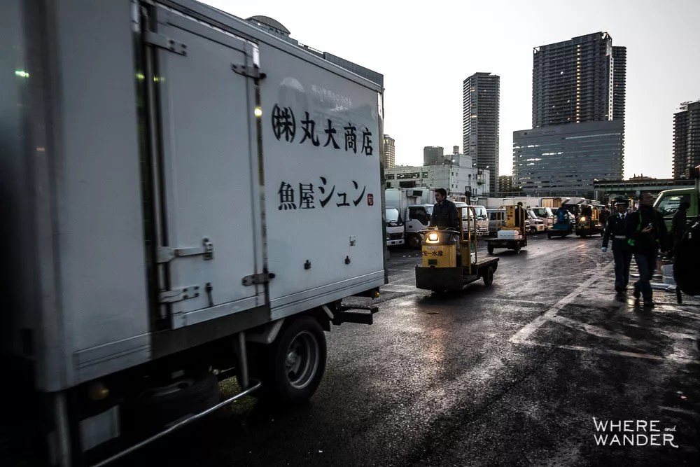 Outside Tsukiji Fish Market At Dawn While Forklifts And Trucks Go By