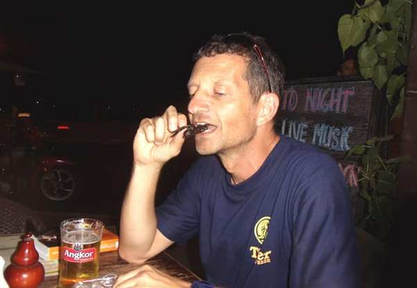Eating a tarantula at a sidewalk café – goes well with cold beer - By Andrew Kolasinski