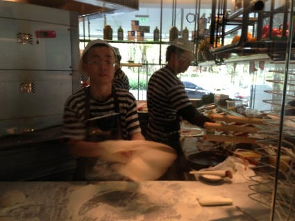 Employees prepare the pizza dough