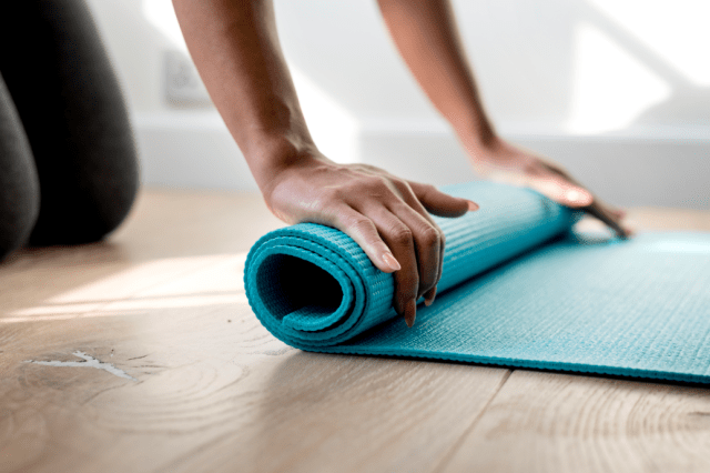 A picture of a woman with a yoga mat