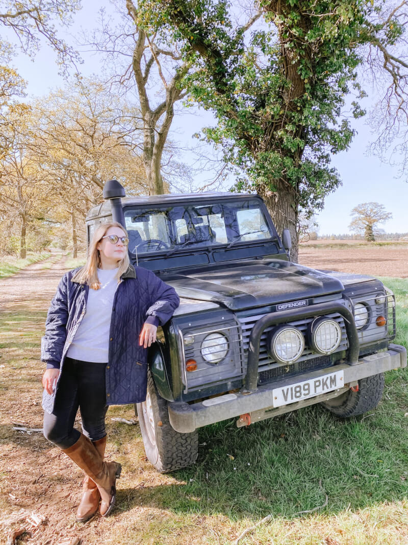 image of woman leaning against a landrover