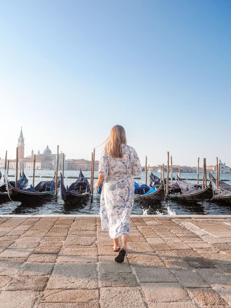 image of woman walking towards gondola's in venice