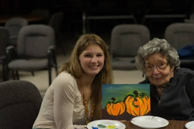 senior citezens with young people and pumpkin paintings