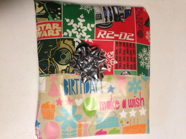 present half wrapped in Christmas paper and half wrapped in Birthday paper