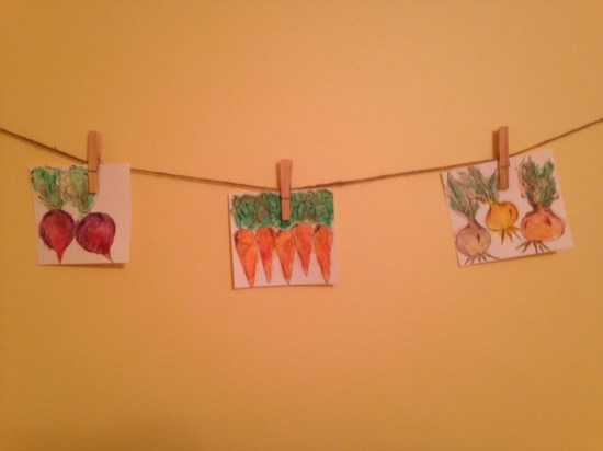 hanging watercolor pictures of radishes, carrots, and onions