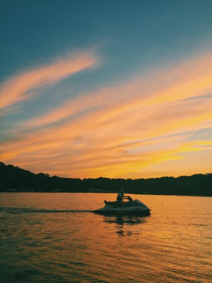 Girl on jetski with sunset in the background