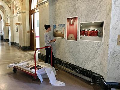 Woman hanging Richard Ross's work