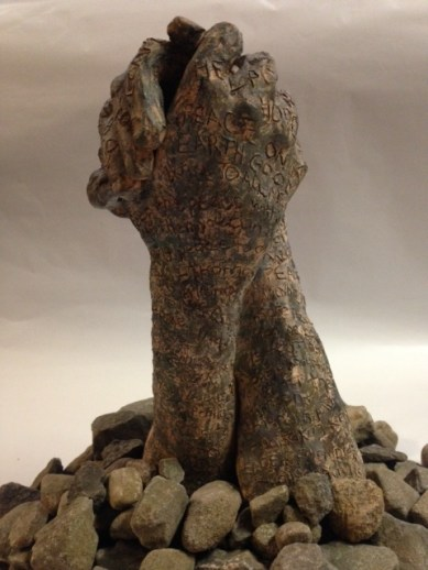 two embracing clay hands appearing like rocks with rocks placed around them