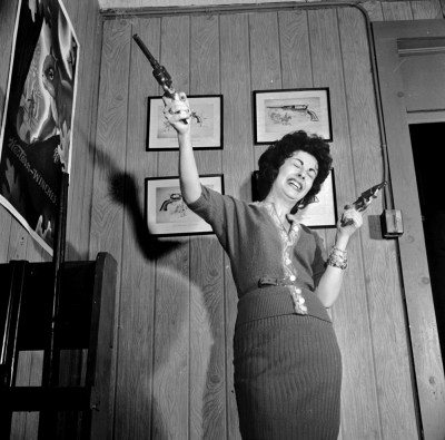 Lola Medina conducting a product demo at the offices of Centre Firearms movie prop gun manufacturer_circa 1955