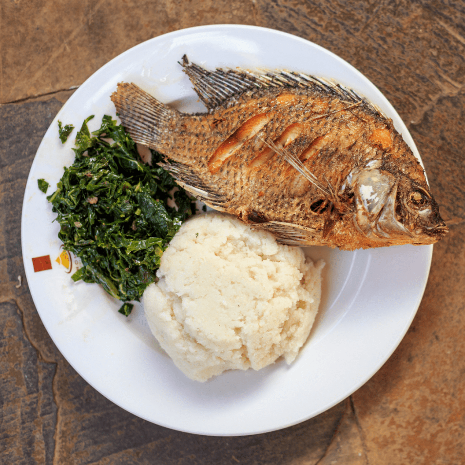 African street food - fish, with ugali and spinach