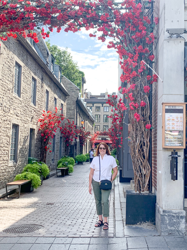 woman standing in front of flower arch in Old Montreal