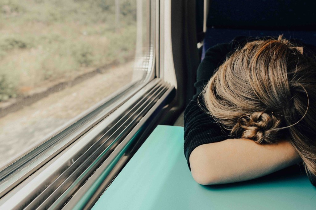 Woman resting her head on a tray.  Traveling for work can be exhausting.