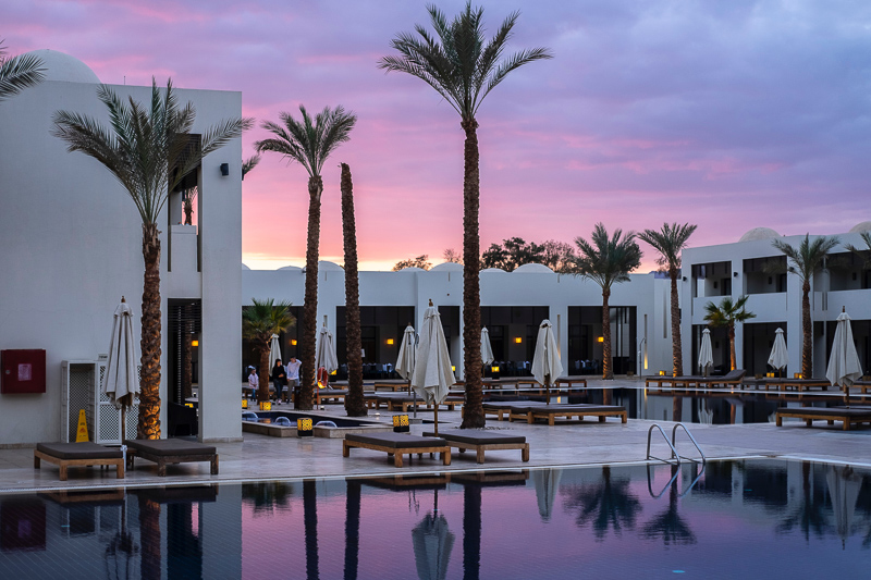 Keeping loyalty points and miles is one of the benefits of business travel.  You could use your points to stay at this hotel with its pool and palm trees at sunset.
