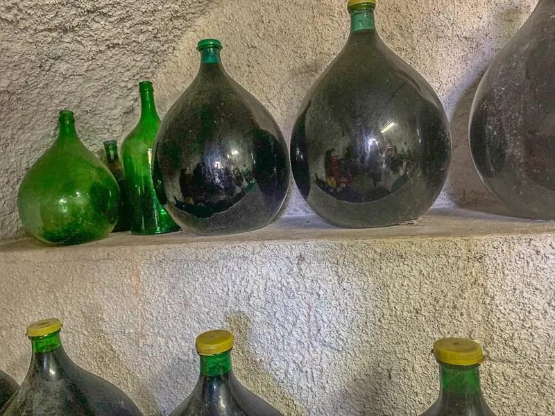 Wine bottles full of homemade wine in a wine cellar in family home in Sorrento, Italy.