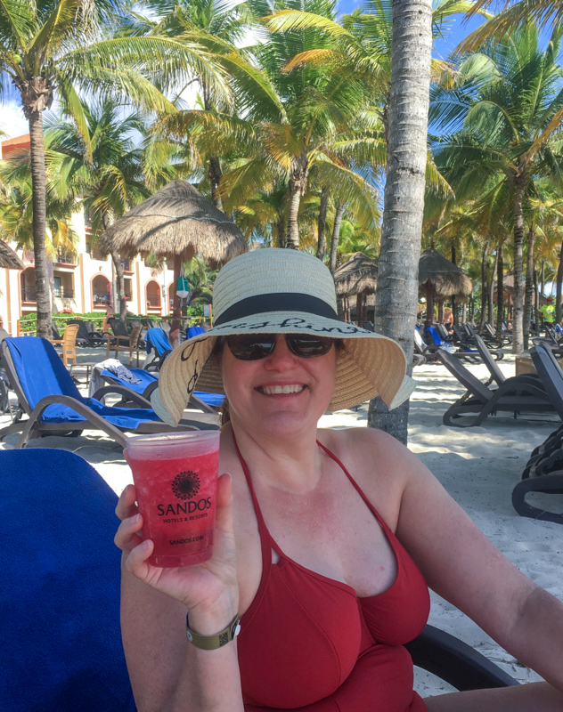 Woman holding a drink on the beach in Mexico.  A hat should be on your Mexico packing list.