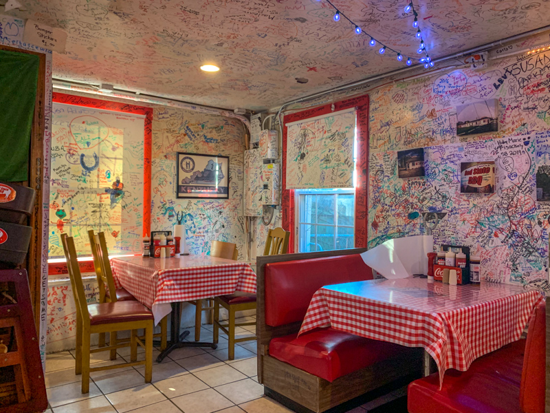 Interior of restaurants with gingham tablecloths and graffiti on the walls.  Red State BBQ is a popular restaurant in Lexington, KY.