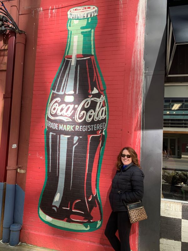 Woman standing in front of a Coke mural in downtown Greenville, SC.  Spend a weekend in Greenville, South Carolina and fall in love!