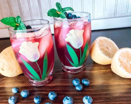 Two glasses of blueberry lemonade surrounded by fresh fruit. Recipe for Homemade Blueberry Lemonade