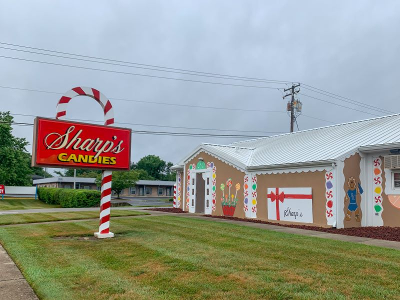 Sharp's Candies in Lexington, KY is painted like a gingerbread house with a large candy cane shaped and painted sign in front. One of the best places to shop in Lexington.