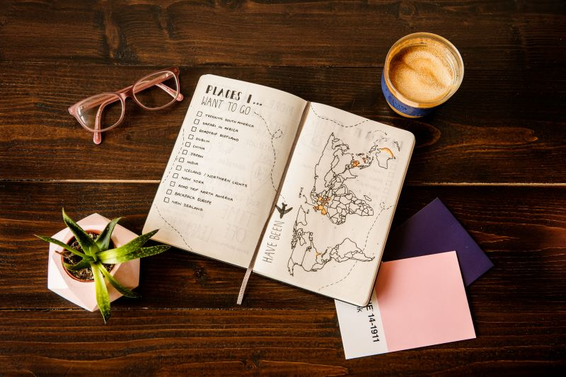 travel journal on a table with drinks, glasses, and a plant. creative travel ideas
