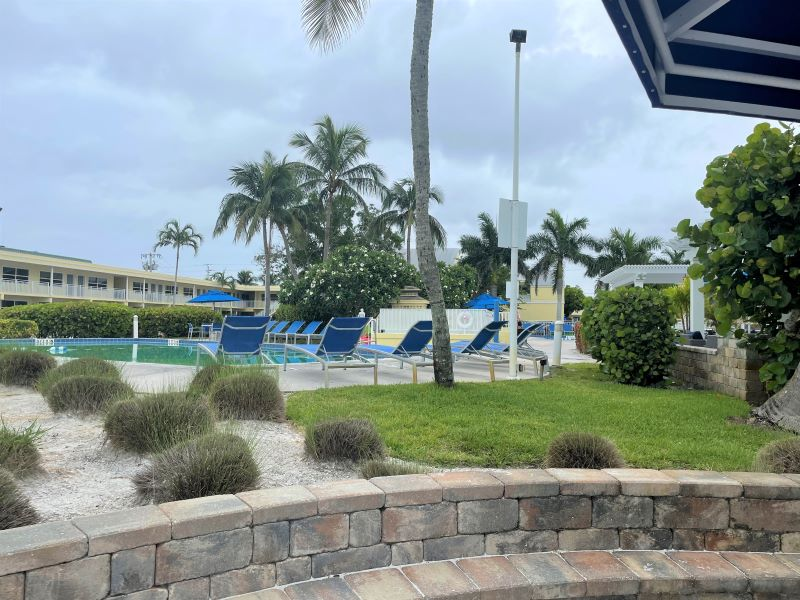 Swimming pool surrounded by blue lounge chairs and palm trees at The Neptune Fort Myers.