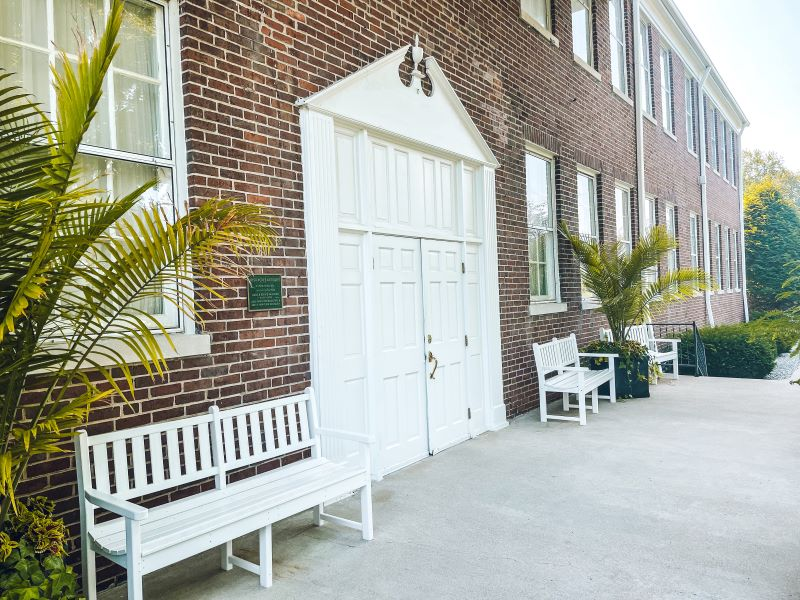 Brick building with a large white door flanked by white benches and plants at Irish Acres in Nonesuch, Ky
