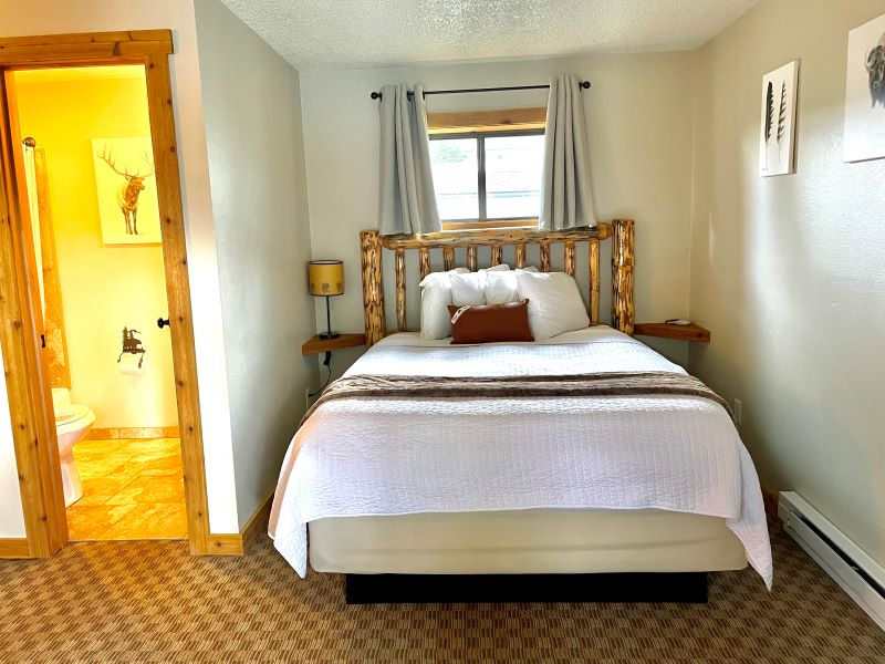 Bed with log headboard and white bedspread at The Evergreen Hotel in West Yellowstone.